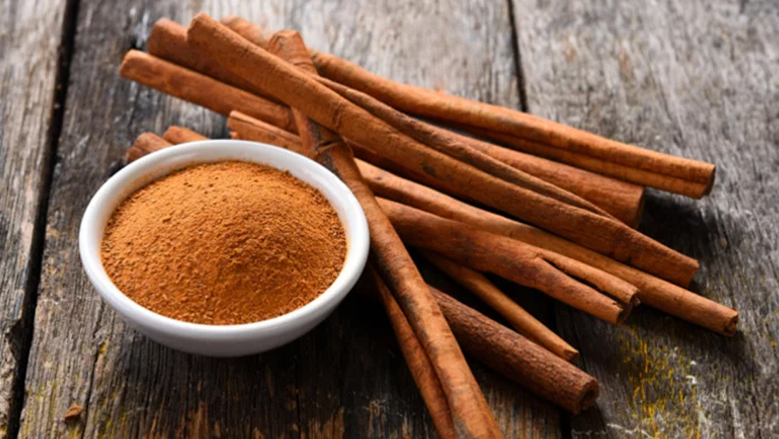 A photo of a cinnamon stick and cinnamon powder in a bowl